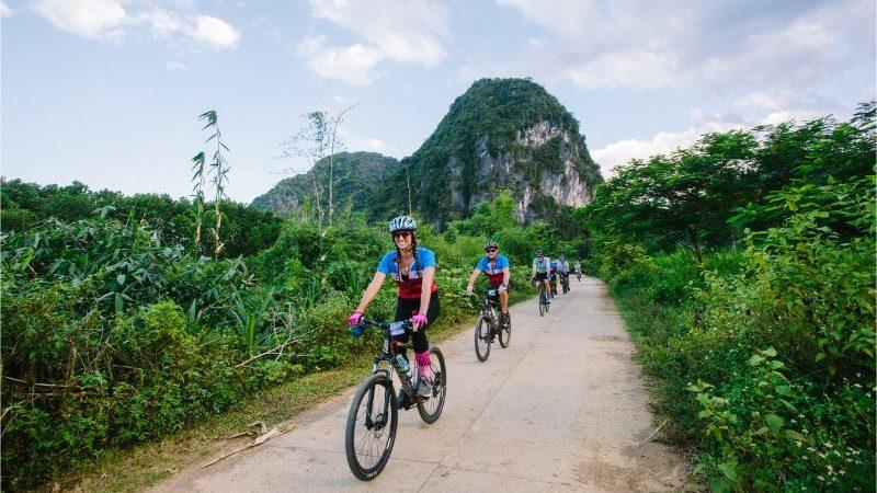 A group of cyclists riding through Mai Chau, Vietnam.