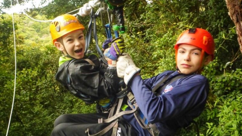 Two boys ziplining in the jungle