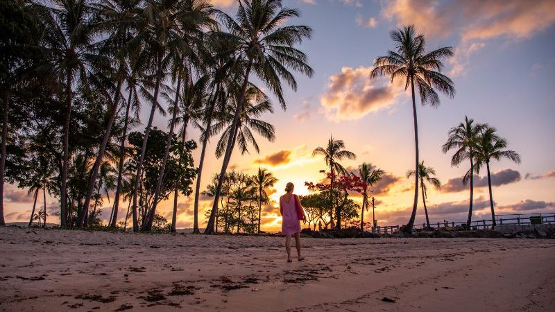 Traveller on the beach at sunset in Port Douglas.