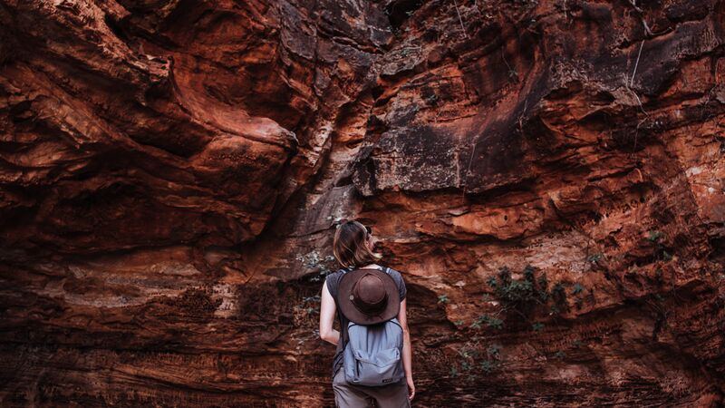 A woman in front of a wall of red rock.