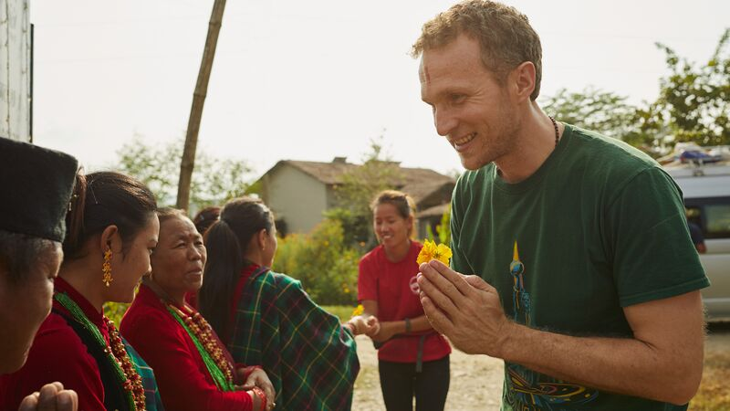 A man being greeted by local women in Nepal