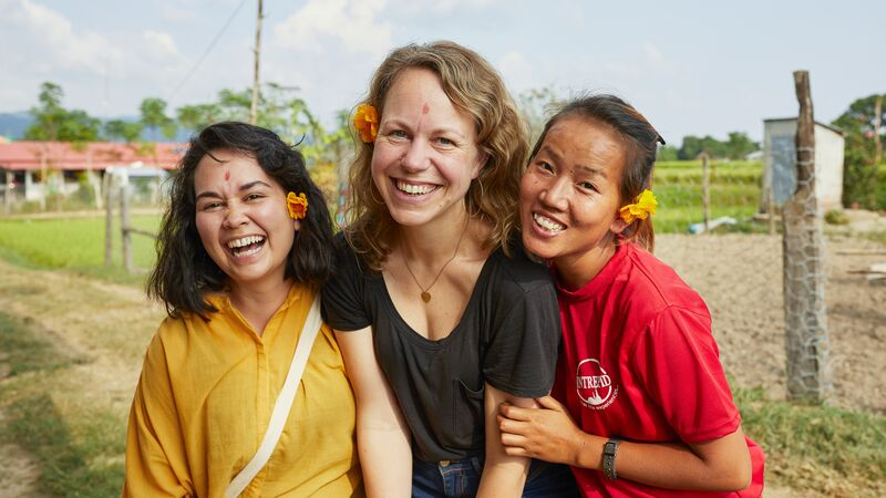 Three smiling women in a small community in Nepal.