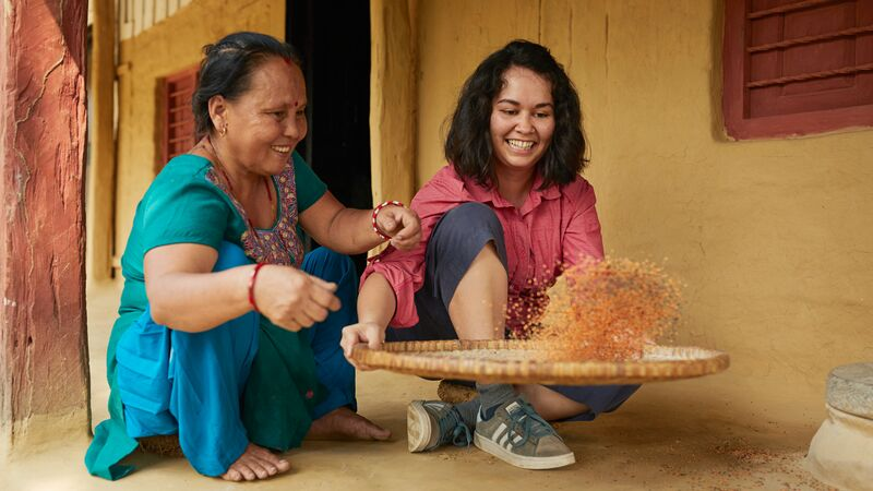 A local woman and traveller split lentils on a basket