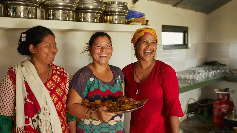 Three women in a kitchen, holding a plate of food, in Nepal.