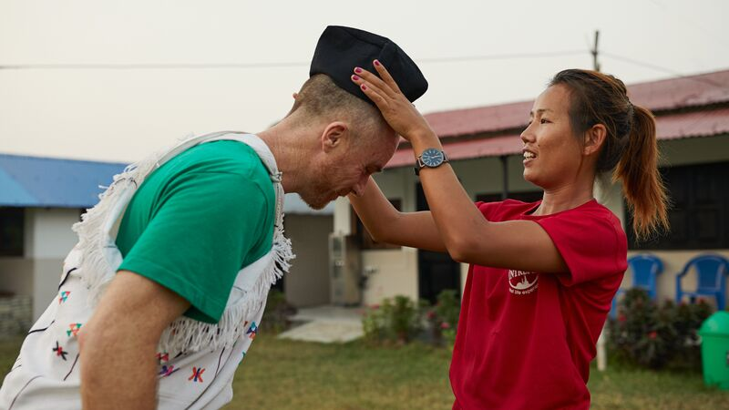 A woman puts a hat on a man in Nepal.