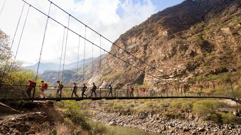 Trekkers crossing a bridge in Peru