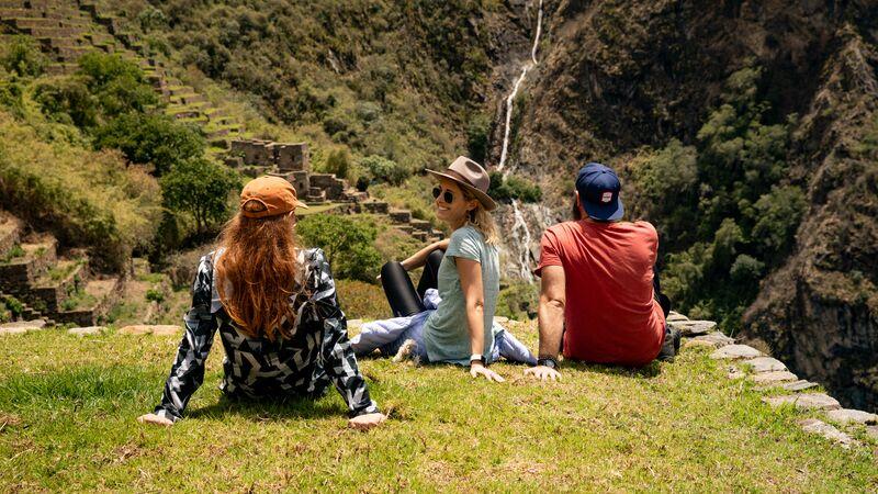 Trekkers sitting on a ledge overlooking Incan ruins in Peru