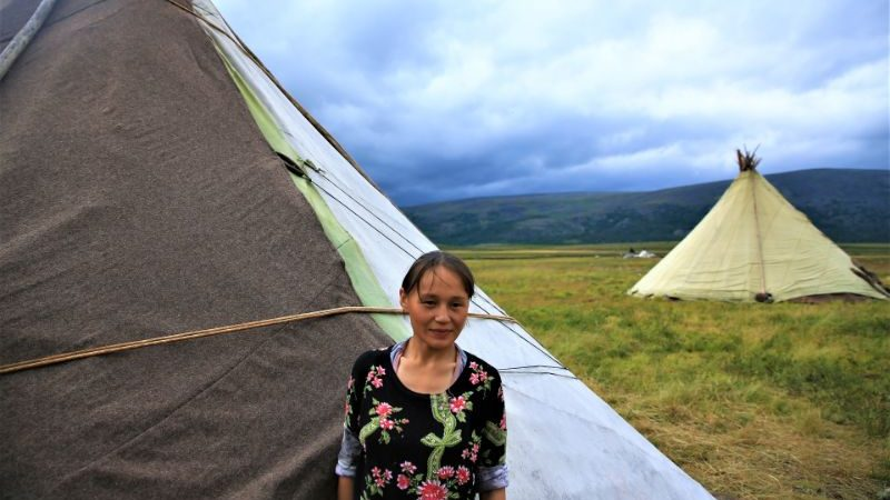 A Nenet woman in Siberia standing in front of her tent