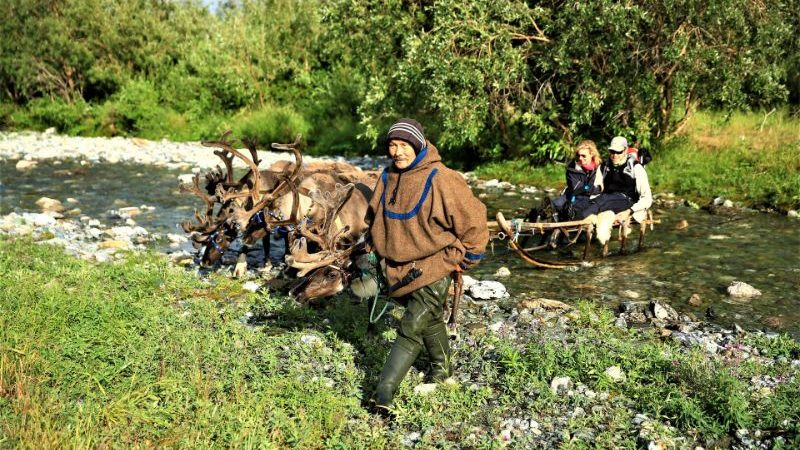 A local man and two reindeer crossing a stream in Siberia