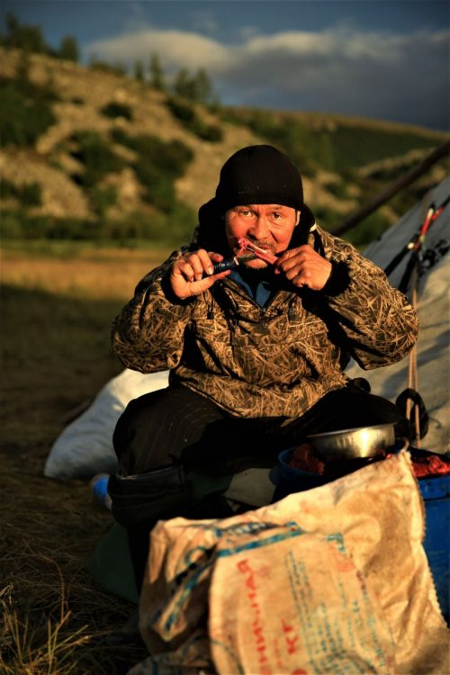 A local man in Siberia eating reindeer