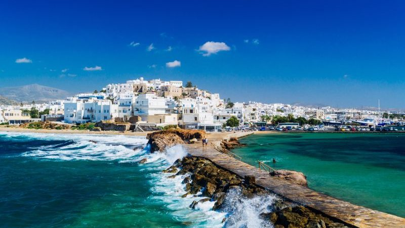View of Naxos town and breaking waves