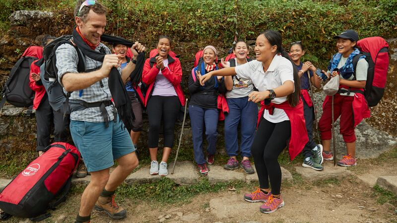A trekker dances on the trail with a female porter