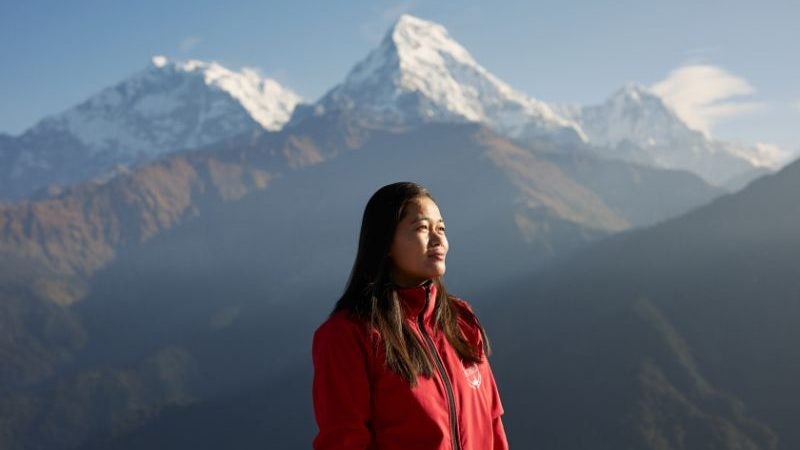 A woman wearing a red jacket with mountains in the background