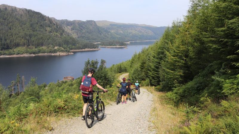 Travellers walking their bikes down a hill