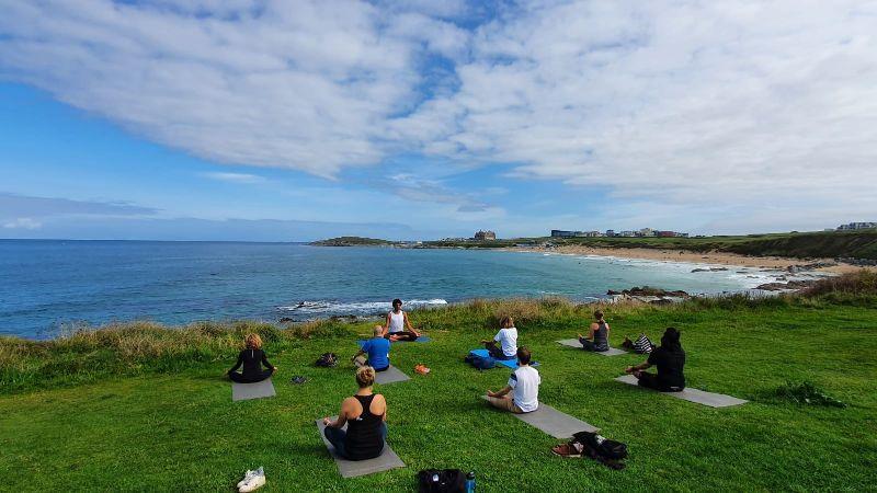 People doing yoga on the Cornish coastline