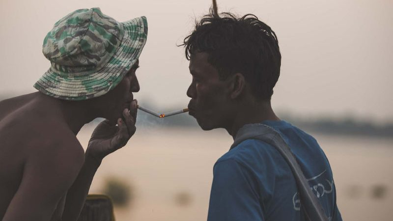 Locals in Myanmar fishing vallage lighting cigarettes