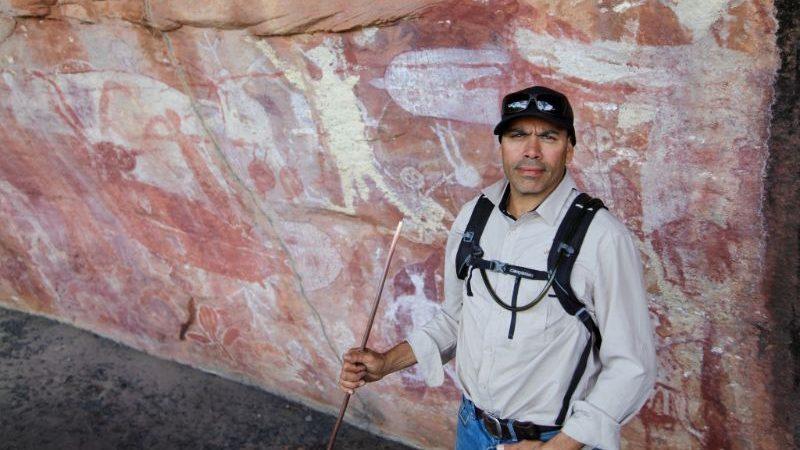 Aboriginal guide in front of rock art