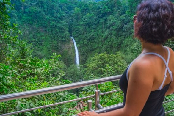 Woman looking out over a jungle and waterfall