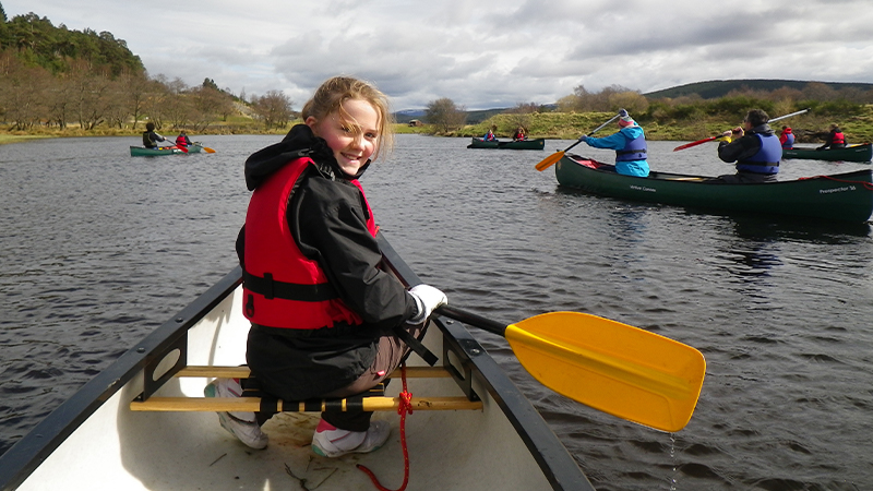 Family canoeing on Caledonian Canal in Scotland