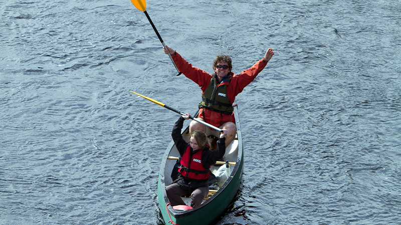 Father and daughter canoeing on Caledonian Canal in Scotland