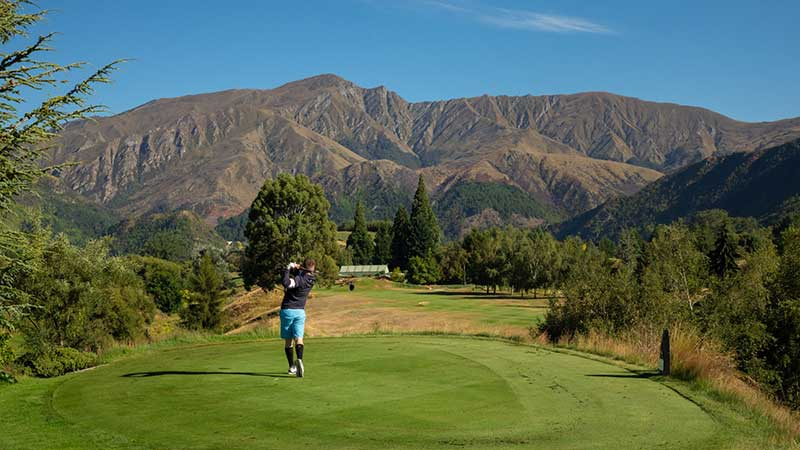 A man taking a swing at the Arrowtown Golf Course in Arrowtown, Queenstown.