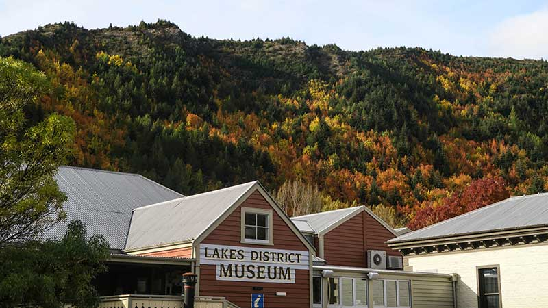 The Lakes District Museum with lush vegetation in the background.