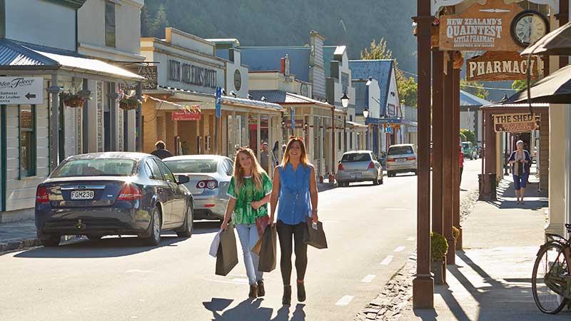 Two women walking down the main street of Arrowtown carrying shopping bags.