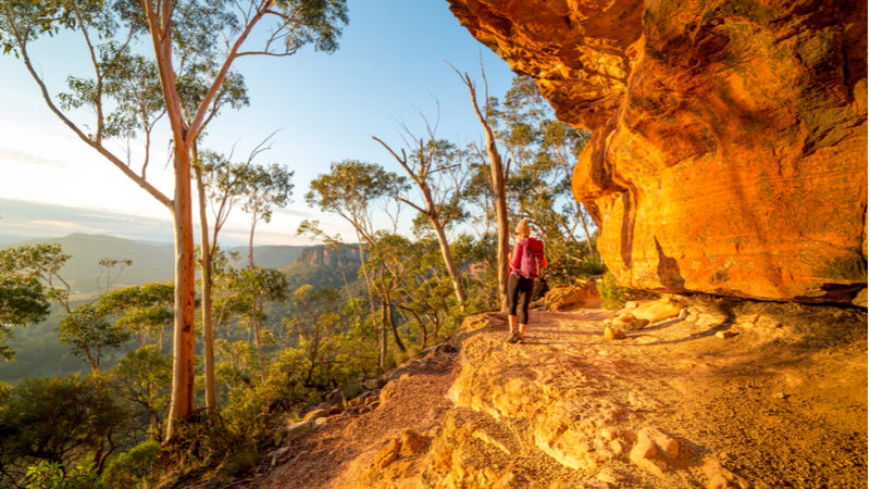 The sun sets on a hiker following the Valley of the Waters walk past sandstone cliffs in the Blue Mountains, New South Wales.