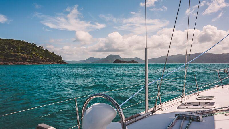 A sailing boat cruising past some Whitsunday islands