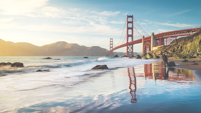 The beach in San Francisco with a view of the Golden Gate Bridge.