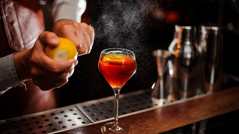 A cocktail being prepared in a dark and moody bar.