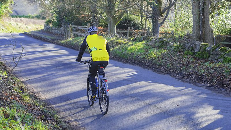 A man cycling through the Cotswolds.