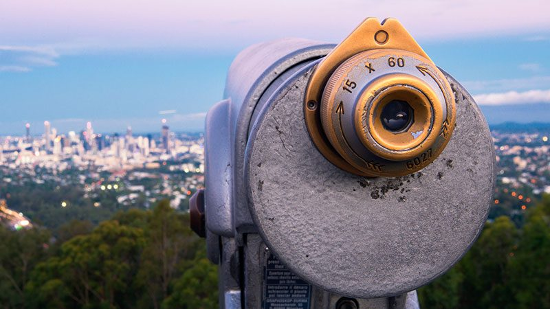 A viewing device points towards Brisbane's city at Mt Coot-tha lookout at sunset.