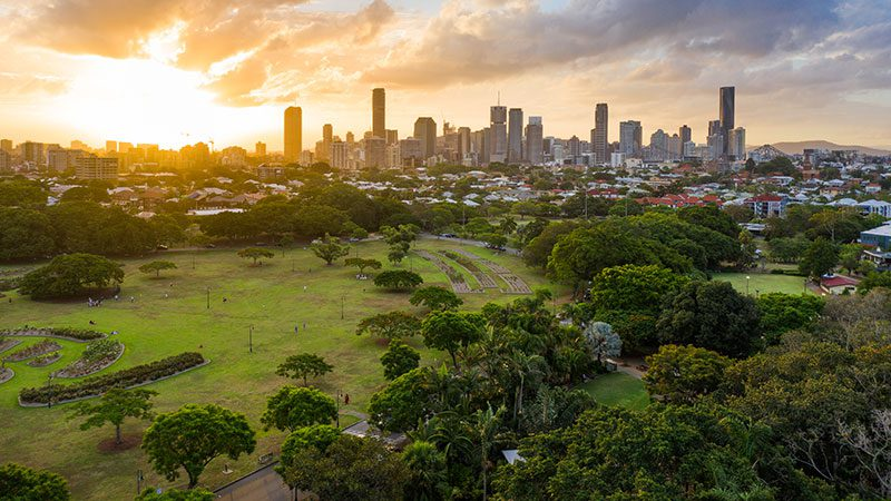 An aerial view of New Farm Park at sunset with Brisbane city in the background.