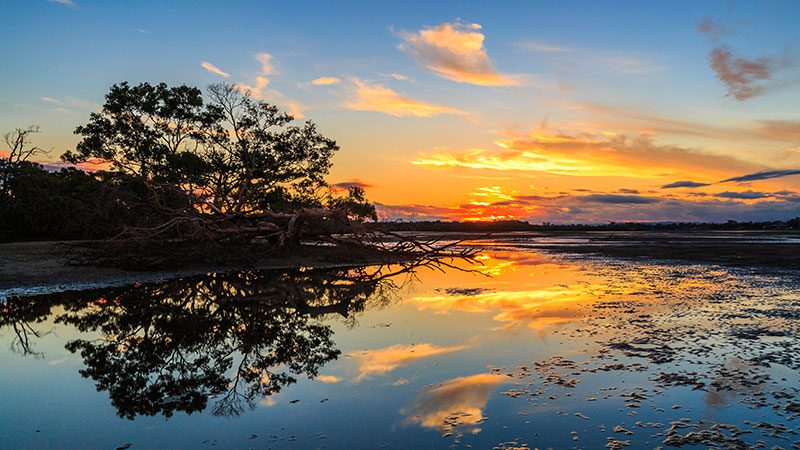 The sun is setting over Nudgee Beach with the colours reflecting on the water.