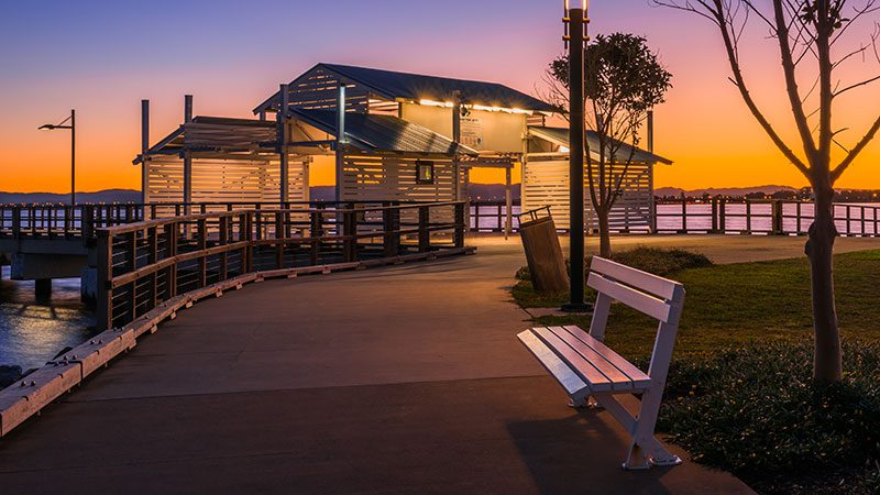 The Woody Point Jetty in Brisbane against a backdrop of a vibrant sunset full of oranges and purples.