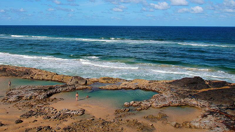 People swimming in Champagne Pools on Fraser Island