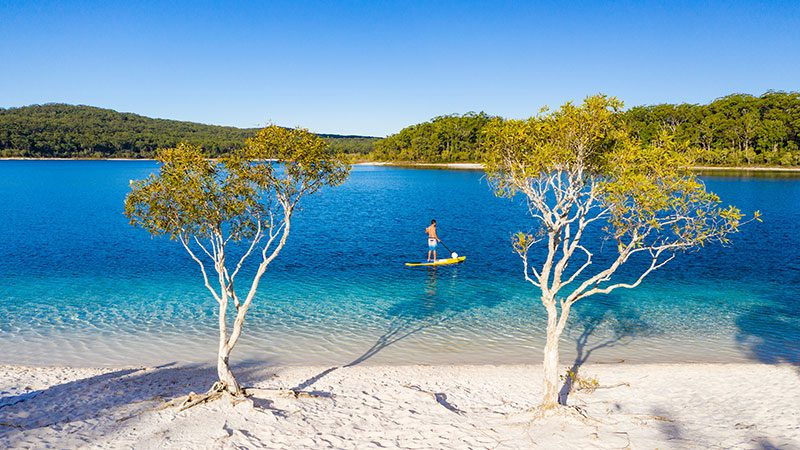 A person paddle boarding in Lake McKenzie