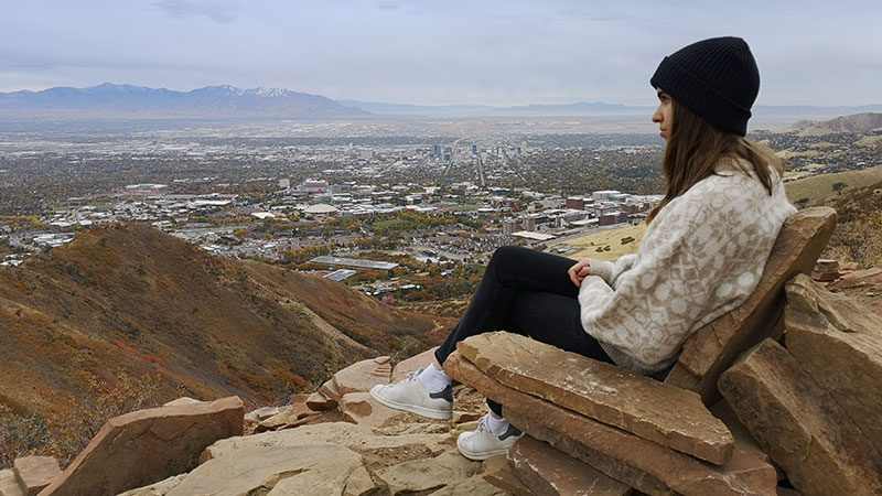 A woman sitting in a seat-like rock formation at the top of the Living Room Hike in Salt Lake City.