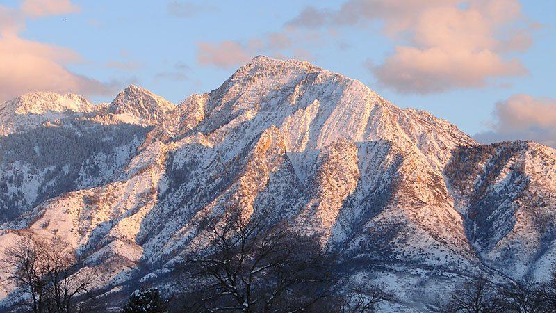 A snow-capped Mt. Olympus in Salt Lake City beneath a setting sun.