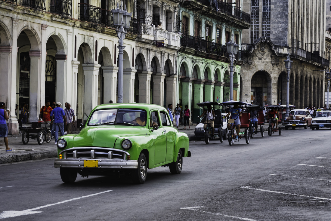 Vintage car riving down busy street in Havana