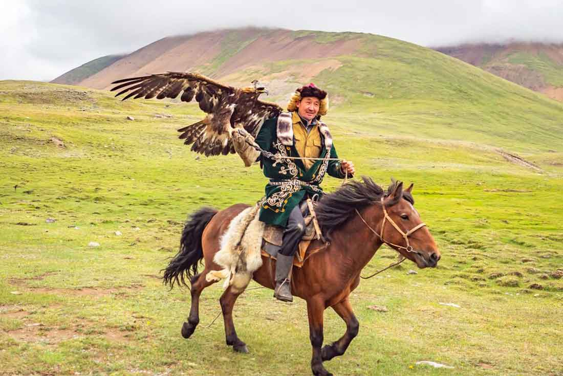 Eagle hunter rides horse in Mongolia