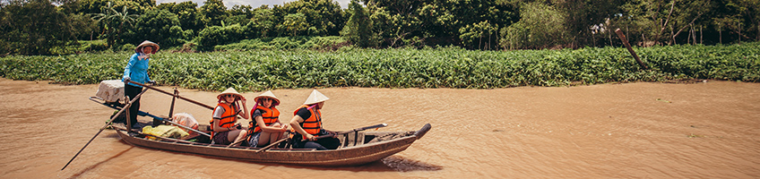 A trio of travellers enjoying a boat road down the Mekong.