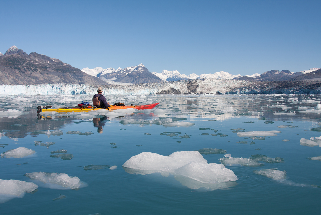Kayaker taking in the mountain views and icy landscape in Alaska