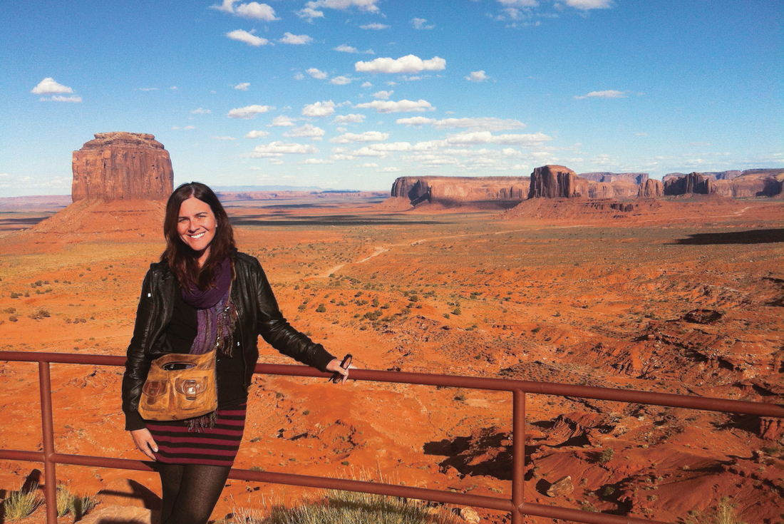 Traveller posing in front of sandstone spires at Monument Valley