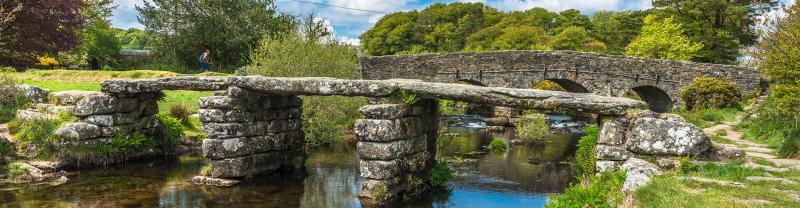 River dart flowing under a bridge with walker in Devon, England