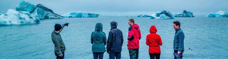 Group of travellers look at Jokulsarlon Glacier from the coastline