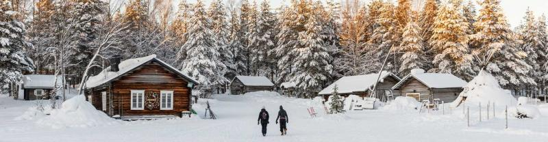 Two travellers walk through thick snow to get to cabin in Finland