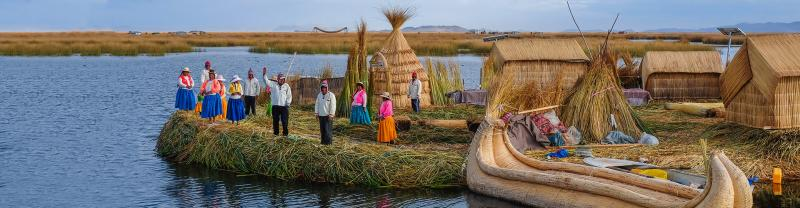 Local villagers wave welcome on floating islands, Lake Titicaca, Peru