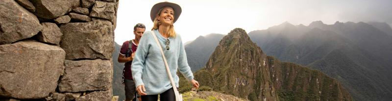 A blonde woman with a blue sweater walk in front of a man in a red t-shirt, with Machu Picchu in the background